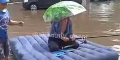 После ливня житель Днепра посреди улицы устроил рыбалку на матрасе: видео