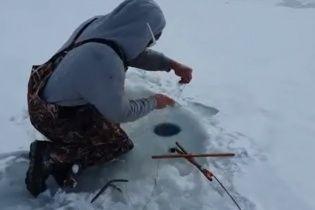 Друг снял на видео, как шокированный рыбак достал из проруби неожиданную добычу