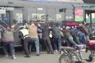 У Китаї заради порятунку чоловіка люди підняли автобус