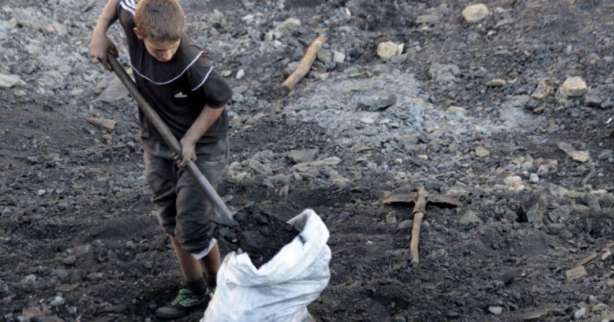 Парень набирает угля в мешок на незаконной копанке возле города Курахово Донецкая область. @ УНИАН
