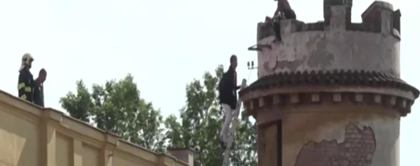 Дивак видерся на вежу в Празі та кидає в людей камінням