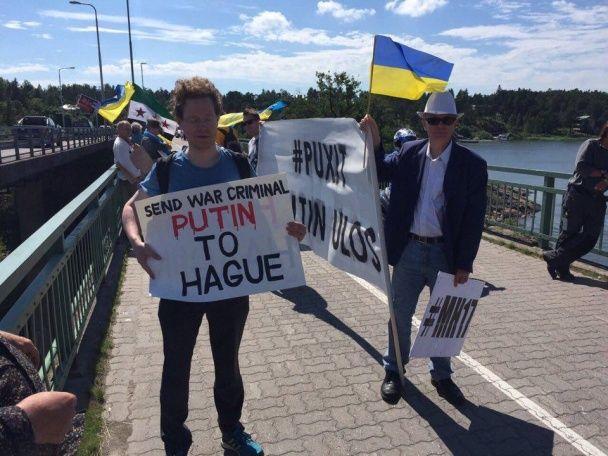 """У Фінляндії Путіна зустріли """"скривавленими"""" плакатами і прапорами України та Сирії"""