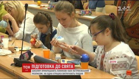 В Днепре школьники разрисовывают елочные украшения уникальной петриковской росписью