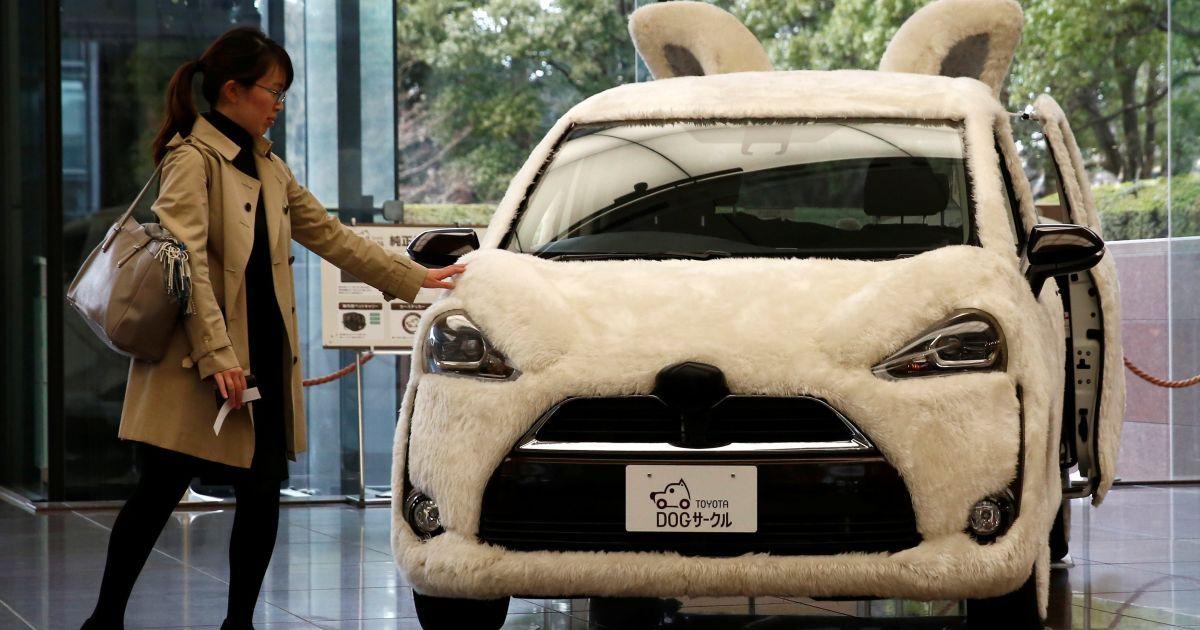 """Жінка торкається машини """"Тойота"""", прикрашеної в формі собаки в штаб-квартирі компанії у Токіо, Японія. @ Reuters"""