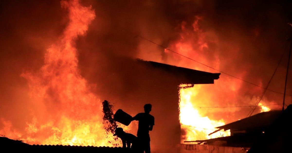 Житель ллє відро води на пожежу в халупах поселенців-сквоттерів, які самовільно захопили землю в місті Малабон, Філіппіни. @ Reuters