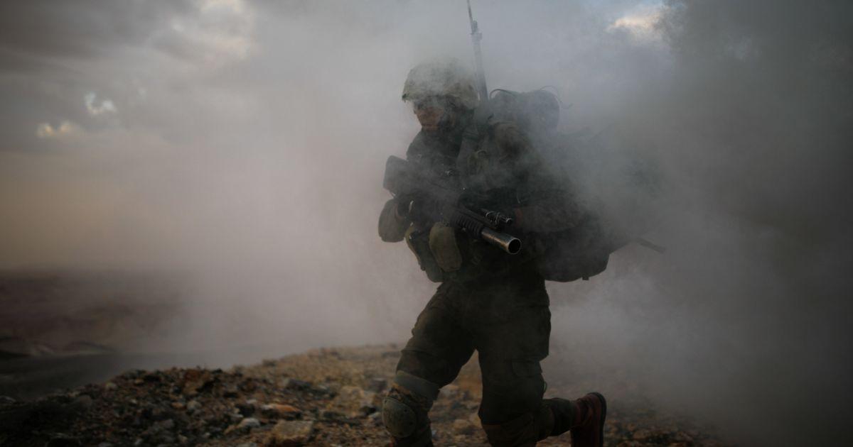 Ізраїльський солдат зі стрілецької бригади  Нахаль проходить крізь дим під час військових тренувань поруч із покинутим готелем в Араді на півдні Ізраїлю. @ Reuters