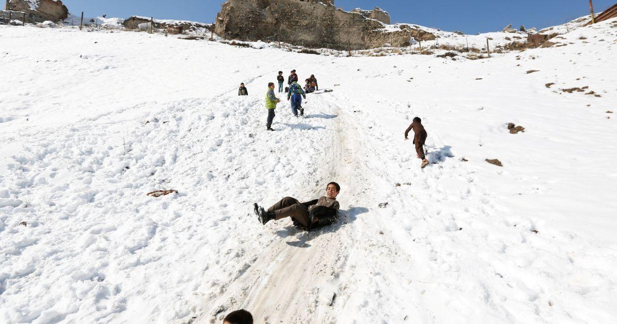 Афганські хлопчики ковзають вниз по засніженому схилу в Кабулі, Афганістан. @ Reuters