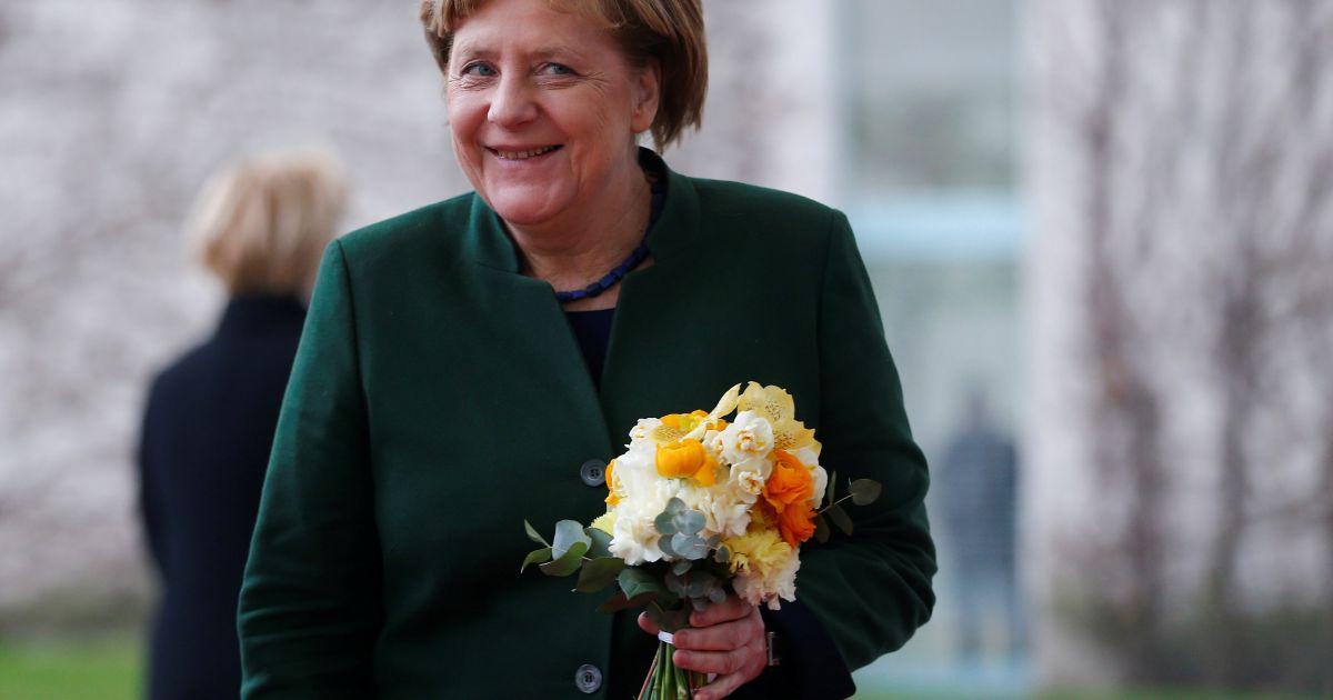 Канцлер Німеччини Ангела Меркель посміхається після отримання квітів від президента Словенії Борута Пахора в рейхсканцелярії в Берліні, Німеччина. @ Reuters