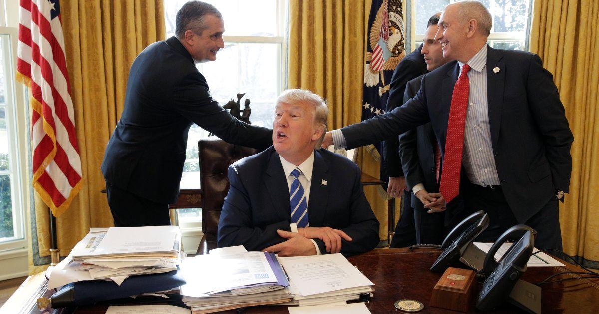 Президент США Дональд Трамп сидить у той час як головний виконавчий директор Intel Брайан Крзаніч вітається з членами Білого дому в Овальному кабінеті Білого дому у Вашингтоні, США. @ Reuters