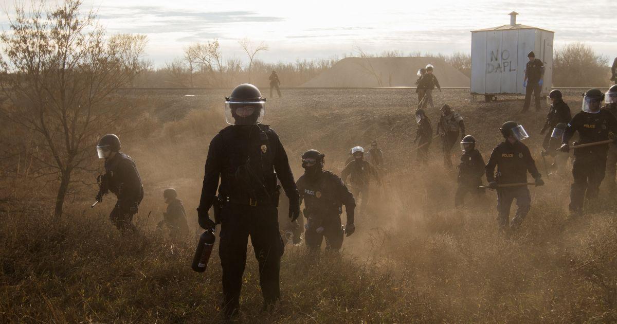 Категорія «Сучасні проблеми». Фоторепортаж. Головний приз. Ембер брейк, Канада - «Стендінг-Рок». Поліцейські розганяють протестувальників неподалік від ділянки нафтопроводу Dakota Access в Стендінг-Роке. Акція проти будівництва нафтопроводу на цій ділянці тривала близько десяти місяців. @ Reuters