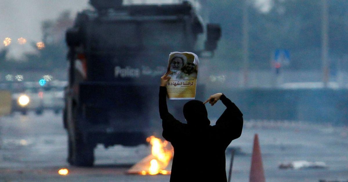 Протестувальниця тримає фотографію шиїтського вченого Іси Квассіма перед бронетранспортером спецпризначенців під час демонстрації з нагоди шостої річниці повстання 14 лютого у Бахрейні. У 2011 році у Манамі почалися акції протесту з вимогою більших прав та свобод, але вони завершилися поразкою демонстрантів. @ Reuters