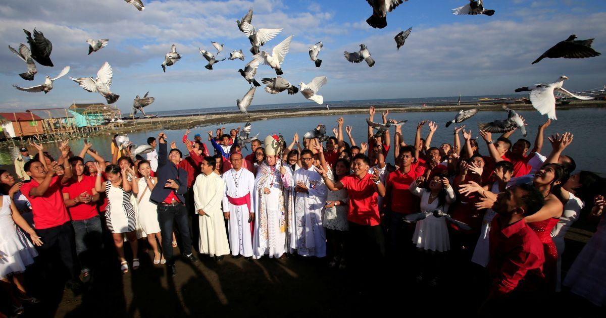 Молодята випускають голубів після масового весілля в рамках святкування Дня святого Валентина в місті Росаріо на південь від Маніли, Філіппіни. @ Reuters