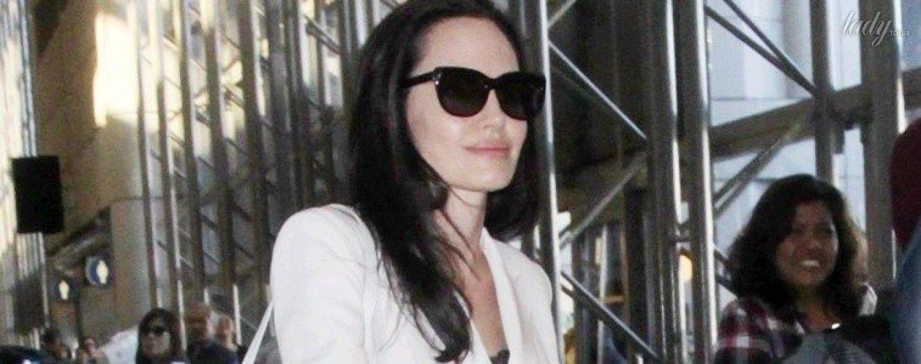 В белом плаще и на каблуках: папарацци сфотографировали Анджелину Джоли в аэропорту