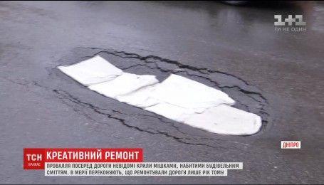 Креативний ремонт: у Дніпрі провалля посеред дороги вкрили мішками зі сміттям