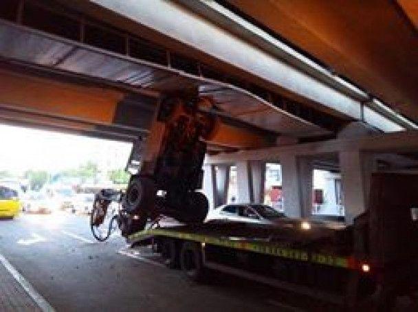 Перевернулся на эвакуаторе: в Киеве погрузчик с поднятой стрелой зацепился об мост