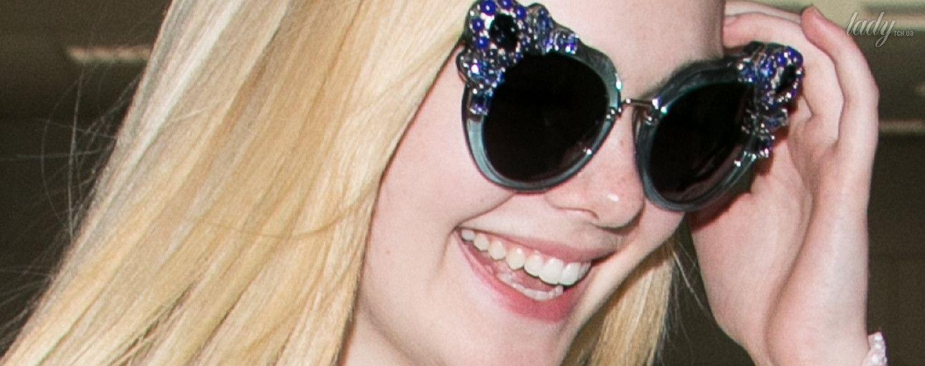 В блузке за 400 долларов и забавных очках: Эль Фэннинг прилетела в Канны