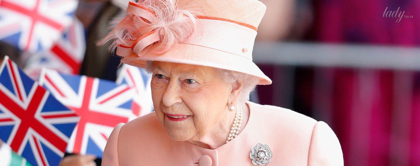 В персиковом пальто и шляпе с перьями: королева Елизавета II в ярком наряде прокатилась на поезде