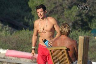 С обнаженным торсом и в красных шортах: Орландо Блум с незнакомками был замечен на пляже