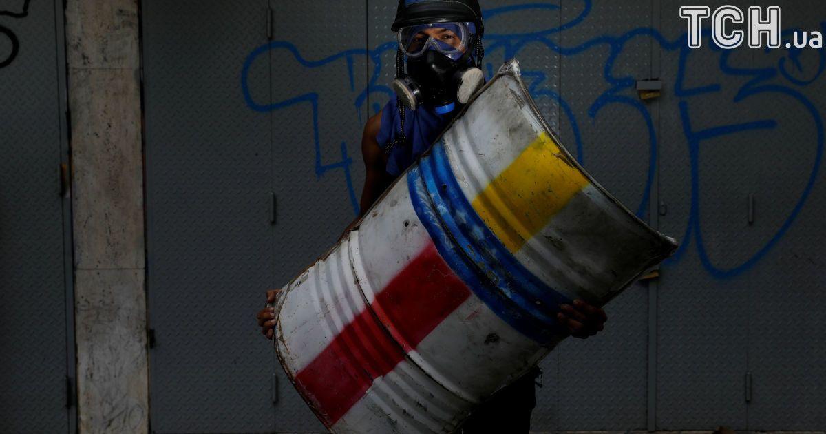 Активист держит щит во время протестов в Венесуэле @ Reuters