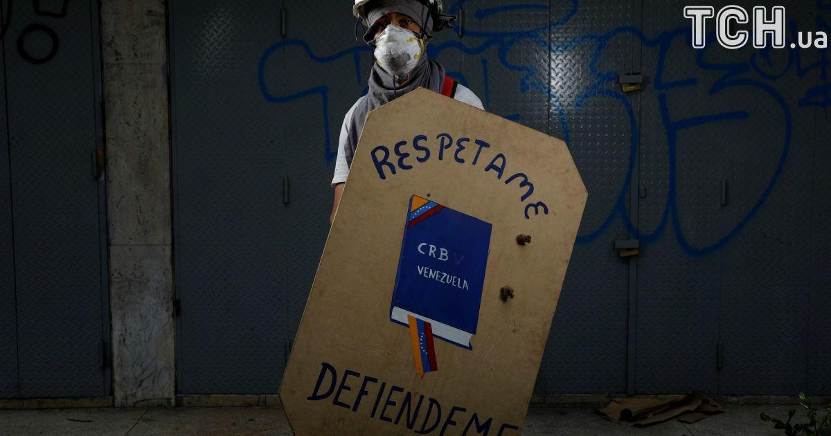 """Активист держит щит с надписью """"Уважай меня, защищай меня"""" @ Reuters"""