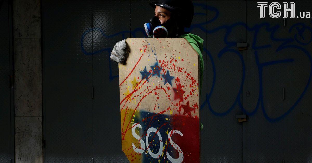 Активист держит щит с надписью SOS @ Reuters