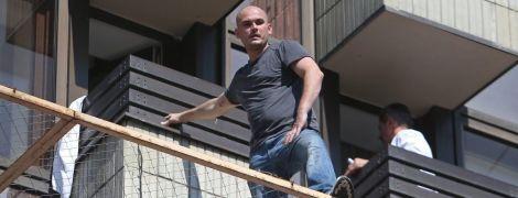 Курить і дивиться вниз. З'явилися фото чоловіка, який погрожує стрибнути з 3-го поверху на Хрещатику