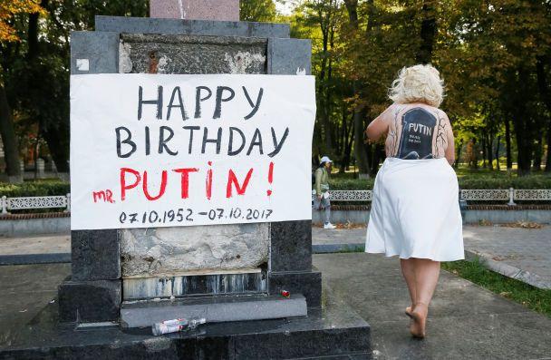 """В центре Киева обнаженная активистка Femen с надгробием Путина на спине, """"поздравила"""" его с 65-летием"""