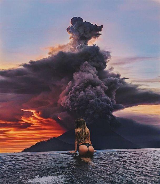 В купальниках и респираторах: туристы массово фотографируются на фоне пробужденного вулкана на Бали