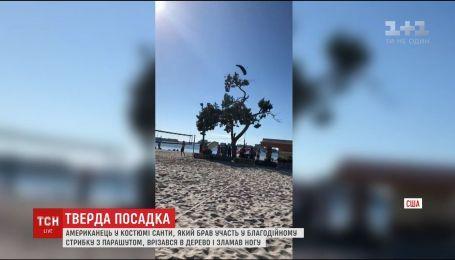 Американец в костюме Санты во время благотворительного прыжка с парашютом врезался в дерево
