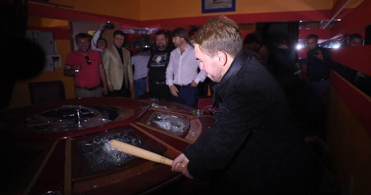 Чоловік із команди Ляшка розбиває ігровий стіл в незаконному казино на Троєщині в Києві @ novostimira.com