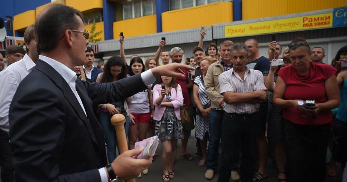 Олег Ляшко тримає пачку грошей, які знайшли в незаконному казино на Троєщині в Києві @ novostimira.com
