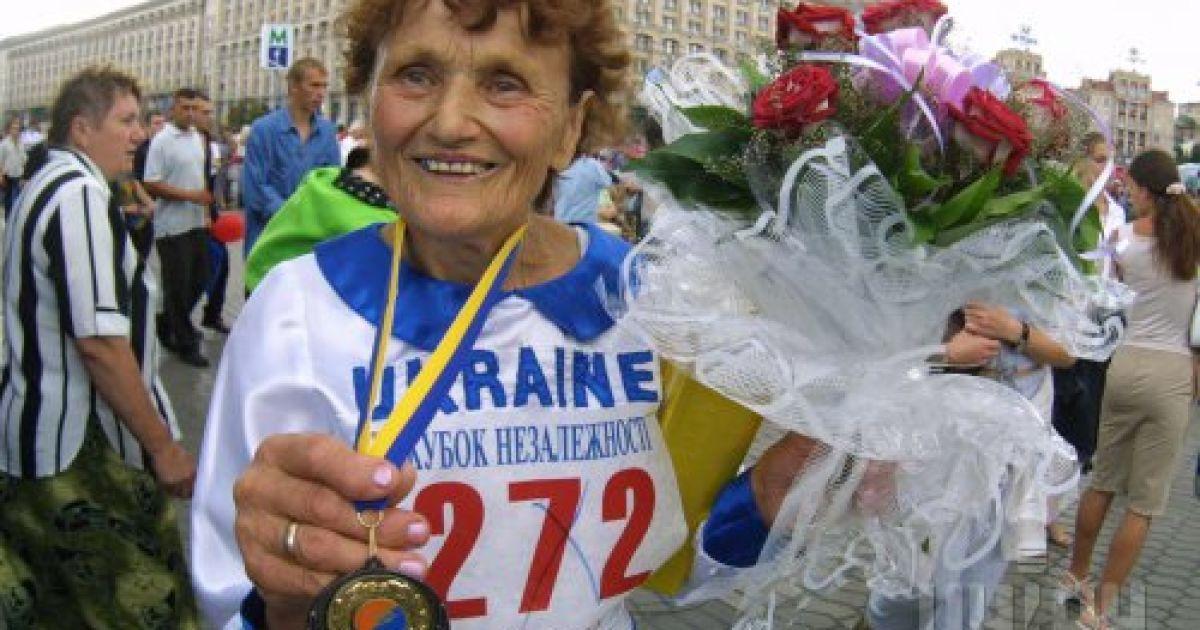"""79-летняя Елена Чуб демонстрирует медаль, которую она получила как самая старшая участница легкоатлетического полумарафона на """"Кубок независимости"""", посвященного Дню Независимости Украины. 24 августа 2003 года @ УНІАН"""