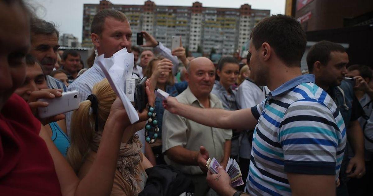 Чоловік із команди Ляшка роздає жителям Троєщини в Києві гроші, які вилучили в незаконному казино @ novostimira.com