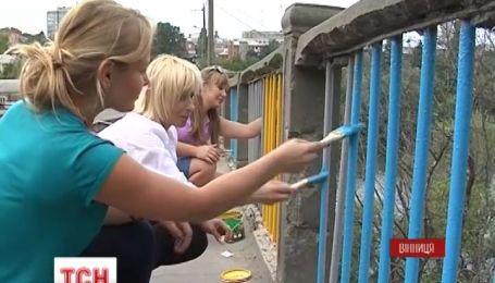 В Виннице раскрашивают скамейки, мосты и здания в сине-желтый цвет