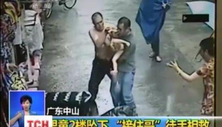 В Китае мужчина умудрился поймать ребенка, который выпрыгнул из окна