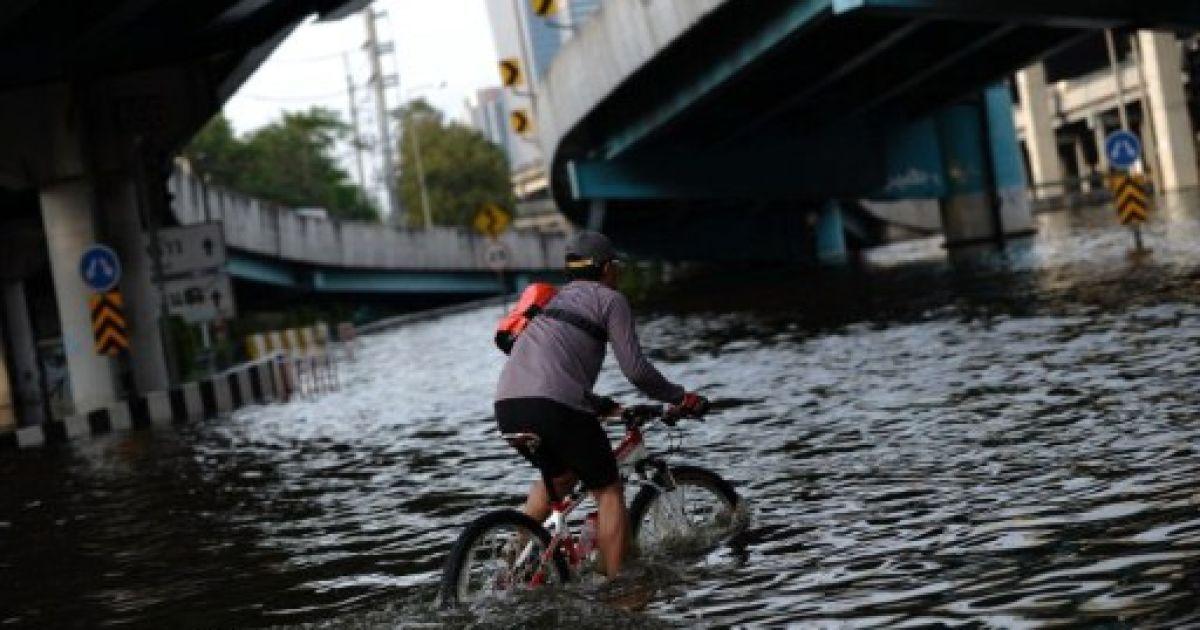 Таїланд, Бангкок. Людина їде на велосипеді проти течії у затопленому в результаті повені районі Mo Чіт у Бангкоку. Більше 529 осіб було вбито під час найгіршої повені в історії Таїланду. @ AFP