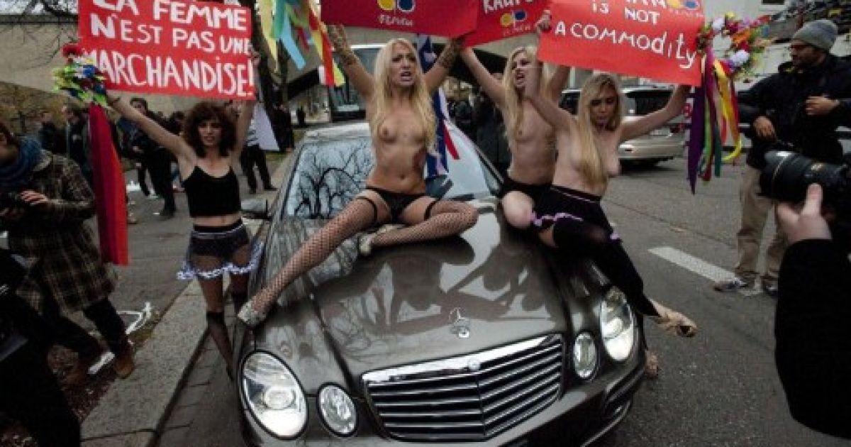 """Швейцарія, Цюріх. Активісти жіночого руху FEMEN тримають плакати з написами """"Жінка — не товар"""" під час топлес-протесту проти проституції та торгівлі жінками, який вони влаштували в районі сутенерів у Цюриху. @ AFP"""