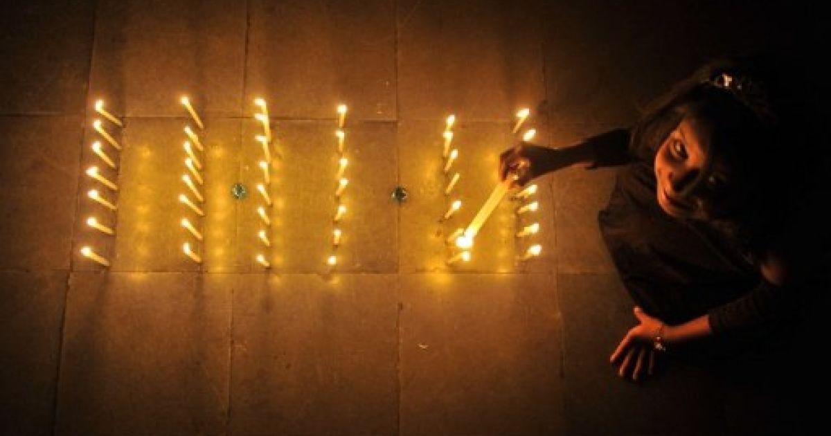 """Індія, Хайдарабад. Індійська дівчинка запалює свічки, виставлені у формі """"магічної дати"""" 11.11.11 у Хайдарабаді. @ AFP"""