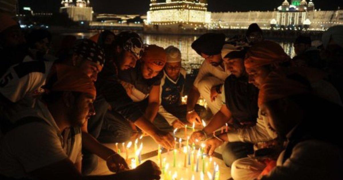 Індія, Амрітсар. Індійські сикхи запалюють свічки під час церемонії вшанування перед Золотим храмом у Амрітсарі. @ AFP