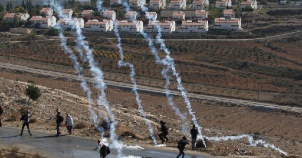 Набі Салех. Ізраїльські солдати кидають каністрами зі сльозогінним газом у палестинських мітингувальників, які відповідають ізраїльтянам камінням під час щотижневої демонстрації проти розширення ізраїльських поселень. @ AFP