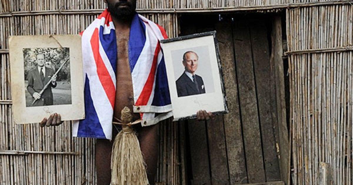 Вануату. Сікор Натуан, син місцевого вождя, тримає два офіційні портрети британського принца Філіпа, стоячи перед хижою вождя у глухому селі на острові Танна у Вануату. У цьому віддаленому селі влаштували яскраве святкування 89-го дня народження принца, і вже готуються до святкування його ювілею наступного року. Адже, мешканці цього селища на острові Танна у Вануату, де чоловіки не носять нічого, крім трави на стегнах, і де всюди ростуть дикі марихуана і тютюн, принцу Філіпу поклоняються як божеству. @ AFP