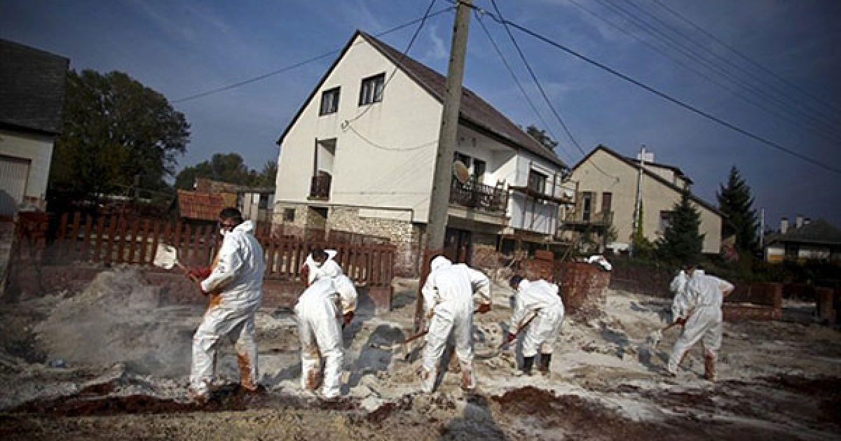 Угорщина, Девечер. Працівники у захисних масках і одязі розкидають гіпс на токсичний червоний шлам, розлитий на вулиці міста Девечер. Угорська влада заявила, що загроза другого виливу токсичних відходів була відвернена, і мешканці зможуть повернутися додому. Завод, який несе відповідальність за аварію, готовий відновити виробництво. @ AFP