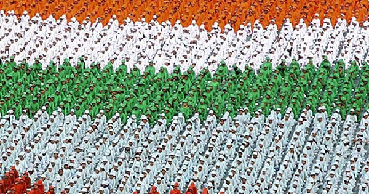 Індія, Делі. Індійські учні у яскравих плащах кольорів індійського прапору під час звернення прем'єр-міністра Індії Манмохана Сінгха до свого народу з привітаннями на честь Дня незалежності Індії. @ AFP