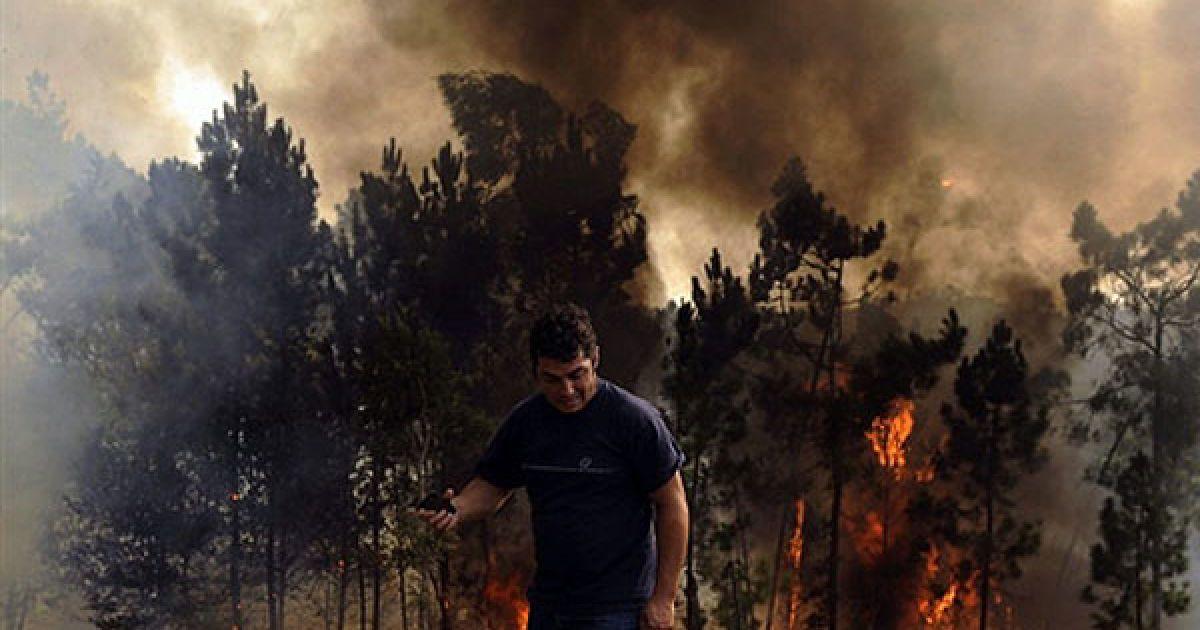 Португалія, Сальвадор. Чоловік з мобільним телефоном йде на тлі лісової пожежі у місті Сальвадор на півночі Португалії. Португальські військові були залучені до гасіння лісових пожеж, які спалахнули на півночі країни. @ AFP