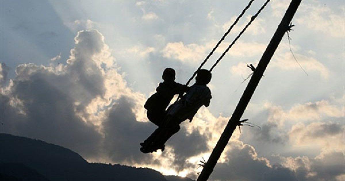 """Непал, Покхара. Непальські діти катаються на гойдалках """"Dashain Ping"""", у місті Покхара, у 200 км на захід від Катманду. У Непалі готуються до святкування індуїстського фестивалю Dashain, який відзначатимуть протягом п'ятнадцяти днів на честь індуської богині влади Дурга. @ AFP"""