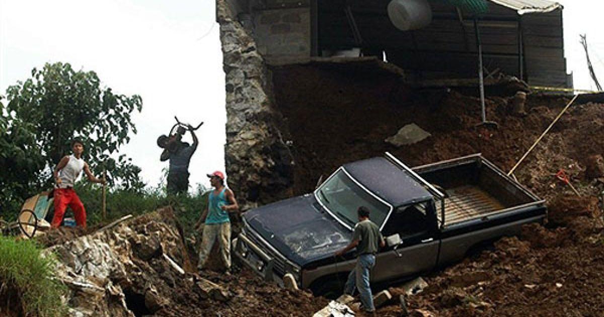Мексика, Халапа. Люди стоять поруч зі зруйнованим ураганом будинком у місті Халапа, штат Веракрус, Мексика. Ураган Карл обрушився на прибережні райони Мексики, що призвело до екстреної евакуації працівників нафтових вишок, закриття атомної станції. Інший гігантський шторм, Ігор, прямує наразі до Бермудських островів. @ AFP