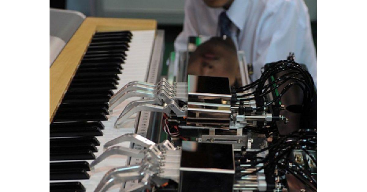 Чоловік спостерігає за грою робота на фортепіано на Виставці роботів у Тайбеї. У виставці взяли участь більше 300 виробників роботів з 66 країн світу. @ AFP