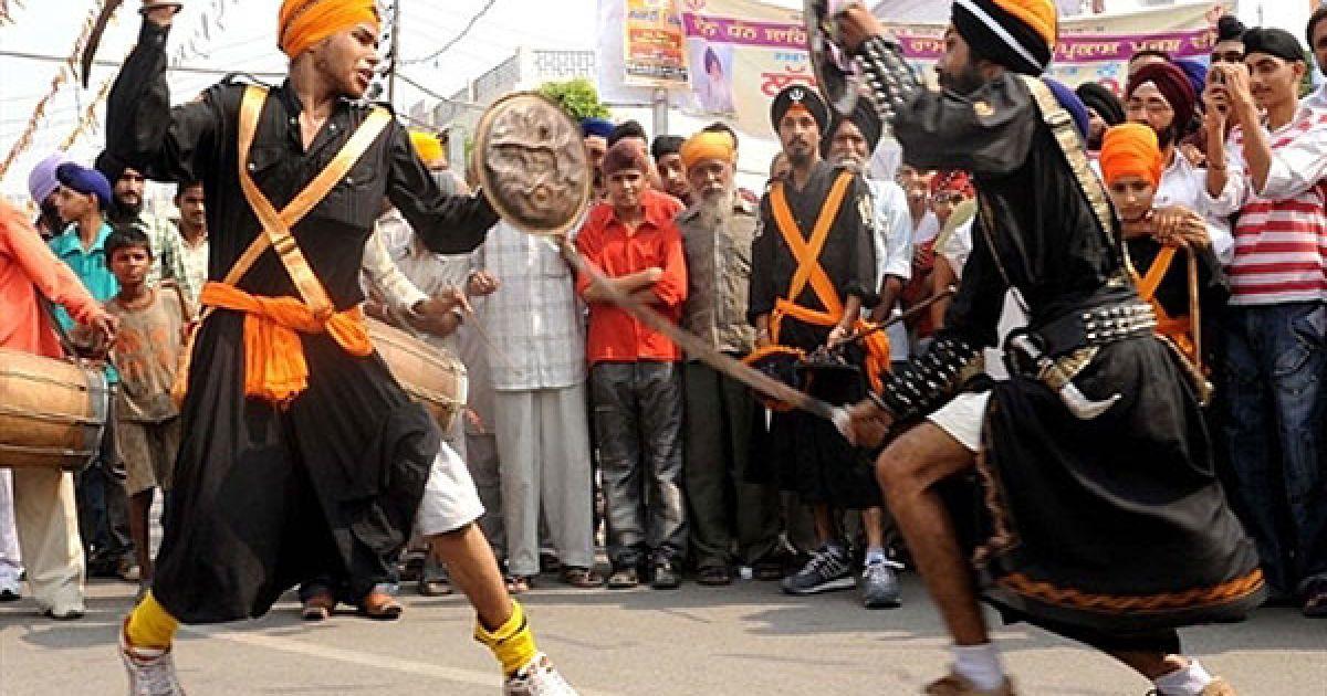 """Індія, Амрітсар. Індійські сикхи, одягнені у костюми релігійних воїнів сикхів """"nihang"""", демонструють свою майстерність у бойовому мистецтві сикхів, відомому як """"gatka"""" під час ходи до Золотого храму в Амрітсарі. В Індії готуються до святкування дня народження четвертого Гуру сикхів Рамдасса, який народився у Лахорі у 1574 році. @ AFP"""