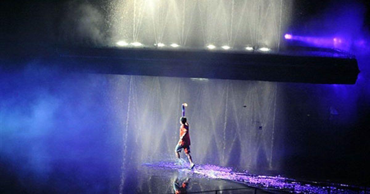 Сінгапур. 16-річний сінгапурець Даррен Чой біжить з олімпійським факелом по воді на урочистій церемонії відкриття Молодіжних Олімпійських ігор 2010 у Сінгапурі. Близько 3600 спортсменів у віці від 14 до 18 років беруть участь у Молодіжних Олімпійських іграх, які одночасно працюють як культурно-освітня програма. @ AFP