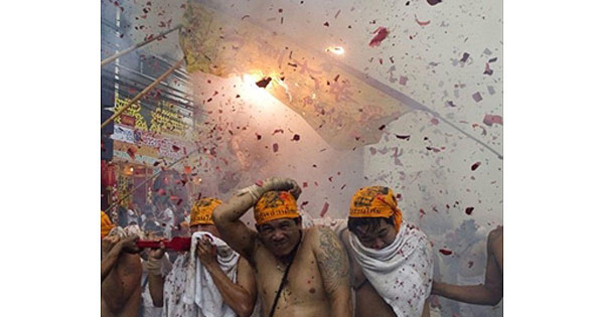 Таїланд, Пхукет. Віруючі несли на плечах паланкін з китайським божеством, коли стався вибух феєрверків. Індицент відбувся під час процесії на честь щорічного Вегетаріанського фестивалю у місті Пхукет. @ AFP